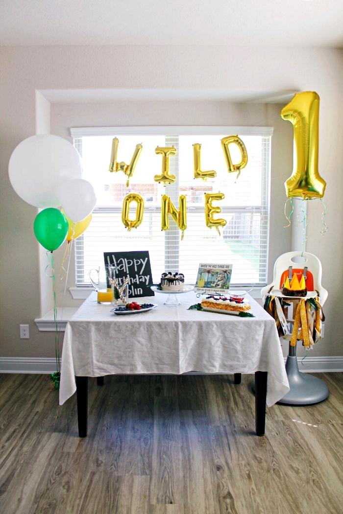 décoration anniversaire 1 an avec ballons mylar chiffres et lettres en or, chaise haute pour bébé décorée d'une guirlande à franges
