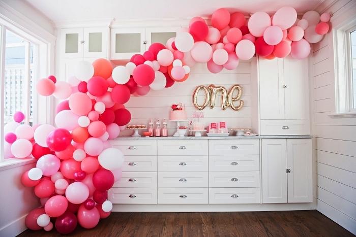une arche de ballons en camaïeu du rose et des ballons lettres pour la decoration anniversaire bébé 1 an