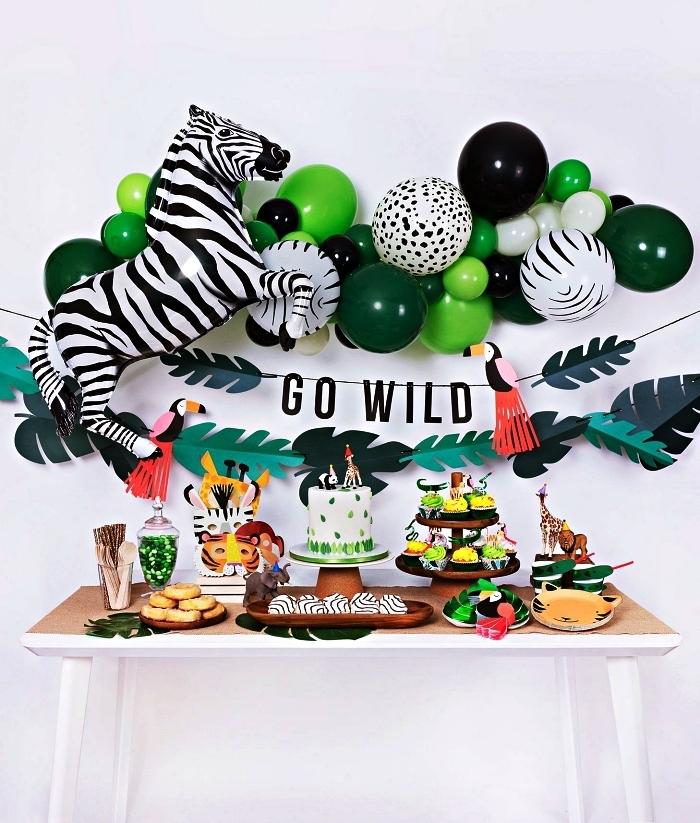 deco anniversaire enfant sur le thème de la jungle, déco murale d'anniversaire 1 an avec une arche de ballons verts et zèbre et guirlande de feuilles tropicales en papie
