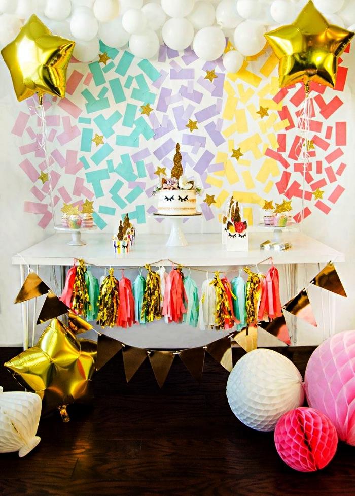 idée déco sur le theme anniversaire licorne, toile de fond de confettis arc-en-ciel et guirlande de ballons blancs pour la décoration du buffet gourmand