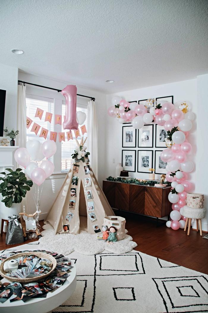 déco d'anniversaire enfant bohème chic avec tipi dans le salon, une arche de ballons en rose et blanc, ballon chiffre aluminium et une banderole joyeux anniversaire 1 an