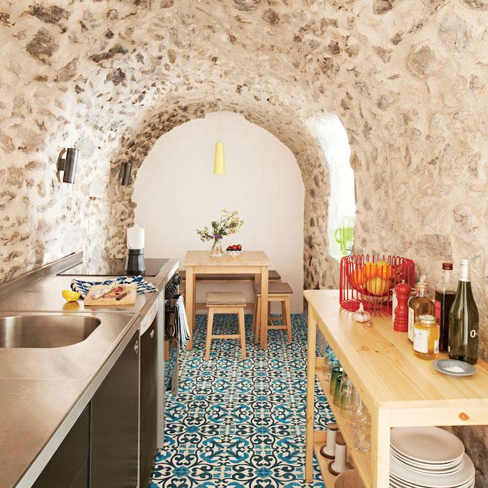 murs de pierre dans une cuisine originale deco marocaine avec carrelage sol mosaique, electromenager inox et table ilot bois