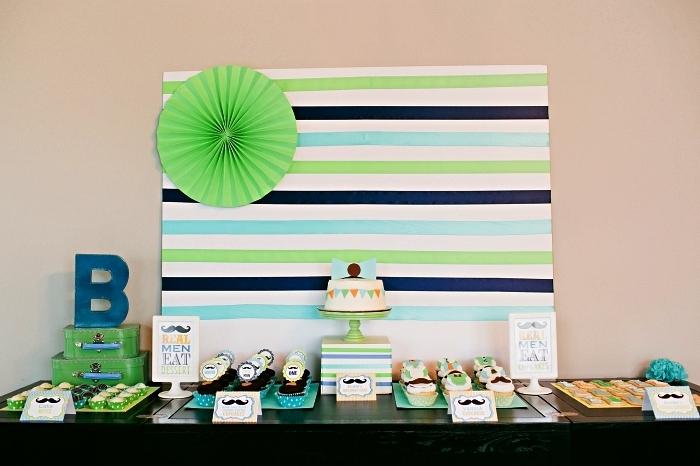 idée de decoration anniversaire 1 an garçon sur le thème moustache, une toile de fond à rayures vertes et bleue pour la déco de buffet d'anniversaire