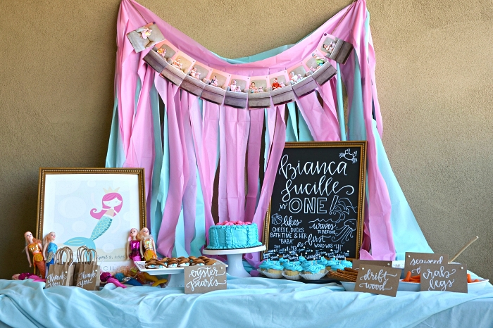 idée pour réaliser une déco de table sur le theme anniversaire petite sirène, candy bar sirène en bleu et rose décoré d'un rideau à franges en toile de fond