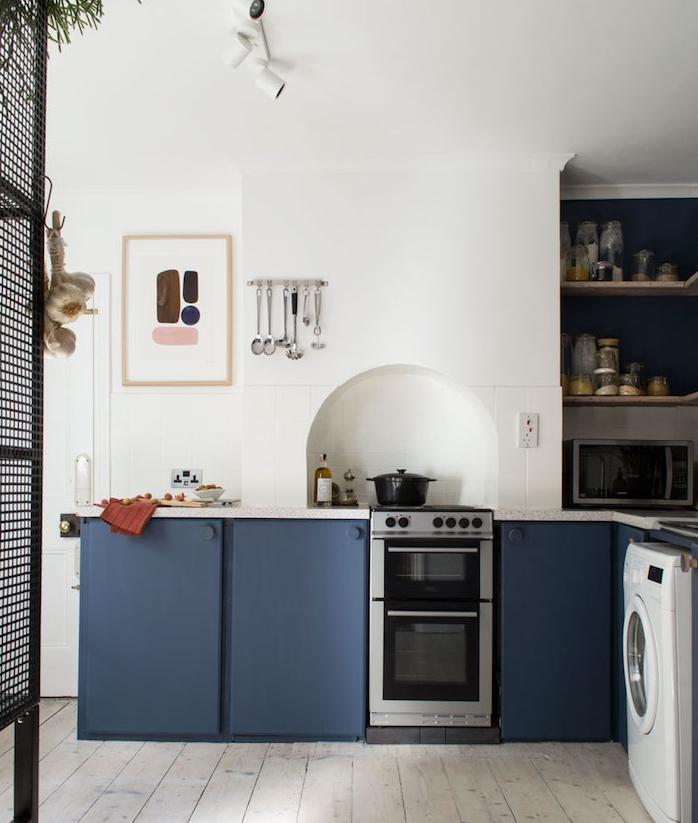 amenagement cuisine bleu nuit et blanc avec une niche murale rangements étagères, murs blancs, parquet vintage