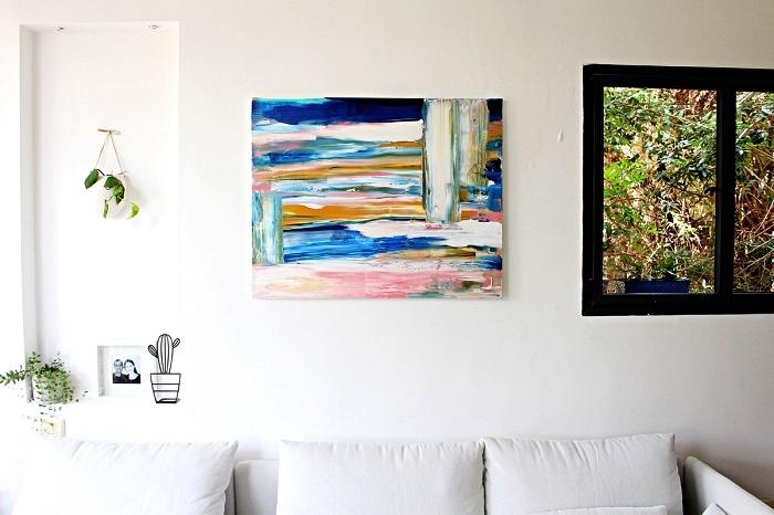 peinture acrylique abstraite sur toile réalisée à l'aide d'une brosse spalter, toile abstraite en nuances de bleu, rose et jaune moutarde