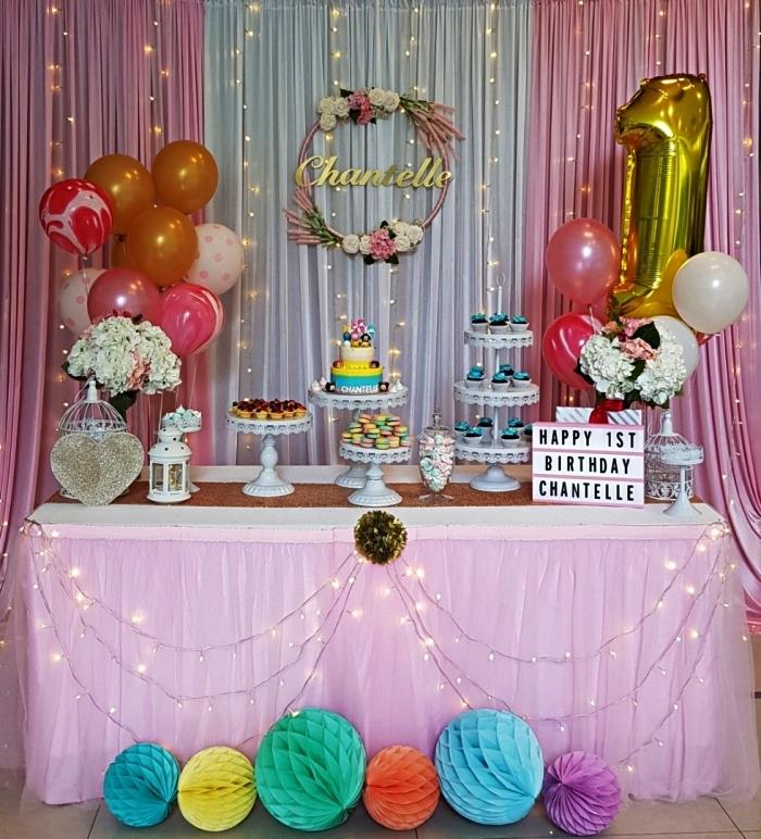 déco d'anniversaire girly en rose et or, sweet table d'anniversaire 1 a, décorée de ballons, guirlandes led, boules alvéolées et une jolie couronne de fleurs personnalisée