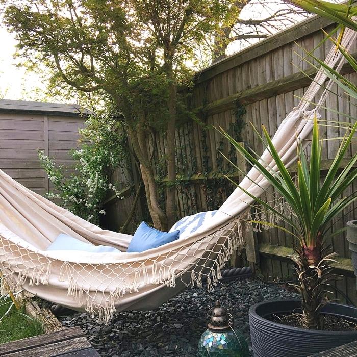 déco bohème dans un petit jardin avec clôture bois et pelouse, modèle hamac macramé pour extérieur décoré avec coussins