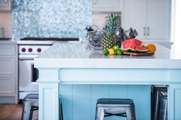 ilot central bleu ciel comme accent dans une cuisine blanche, tabourets de bar couleur grise, fruits tropicales, deco bord de mer