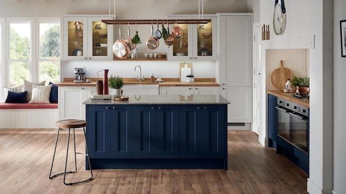 ilot de cuisine bleu nuit dans une cuisine blanche avec des ustensiles suspendus d une échelle flottante, parquet bois foncé, murs blancs