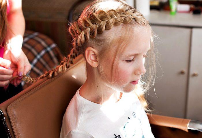 Blonde fille cheveux longs, tresse indienne, coupe de cheveux petite fille, blouse blanche, fille assise sur une chaise en cuir