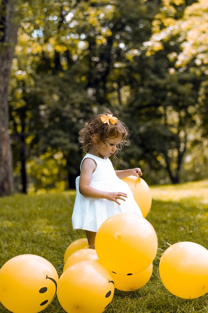 Le premier anniversaire party avec ballons jaunes, jardin fille qui joue avec ballons, fillette robe blanche, coiffure cheveux bouclés, papillon jaune mignon