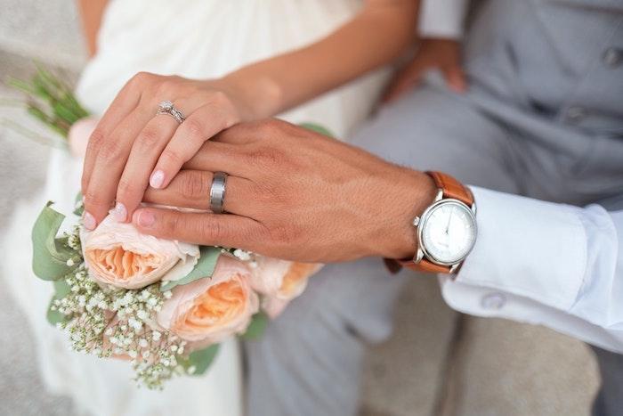 Main dans la main, deux alliances de mariage classiques en platine, femme et homme mariage bouquet