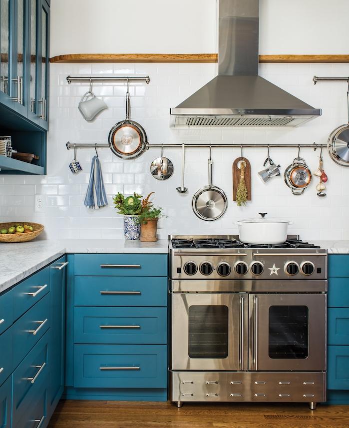 exemple de cuisine bleu canard avec credence carrelage blanc, vaisselle et ustensiles de cuisine suspendus, electromenager inox, parquet bois foncé