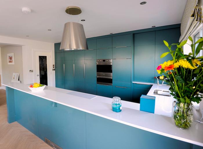 amenagement cuisine bleu canard avec des plans de travail blanc laqué, suspension grise énorme originale, parquet bois clair