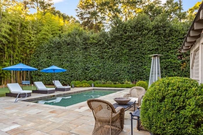 idée deco piscine avec terrasse en dalle, modèle transats piscine tressés avec matelas blanc et parasol en bleu