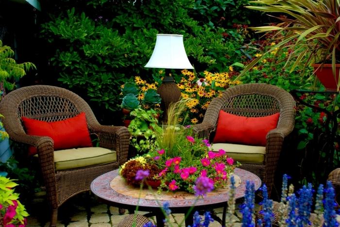 idee amenagement jardin à espace limité, mobilier de jardin tressé en marron décoré avec coussins en vert et rouge
