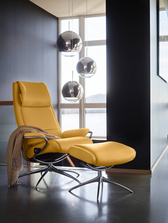 design intérieur moderne dans un salon aux murs foncés avec lampes suspendues, exemple de fauteuil relaxant avec repose-pied en cuir jaune moutarde