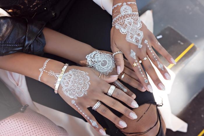 exemple de tatouage au henné pour main, idée tattoo éphémère en blanc aux motifs flèche et mandala à effet bracelet