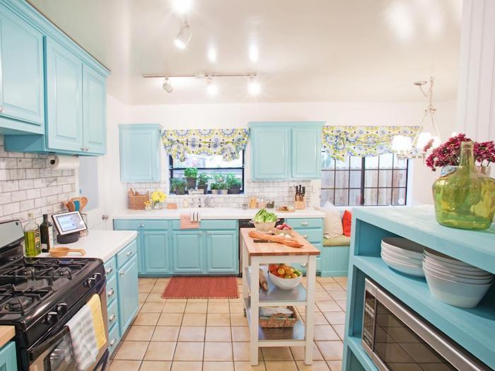 cuisine bleu clair sur la facade, carrelage beige original, ilot établi bois, rideaux colorés de fenetre