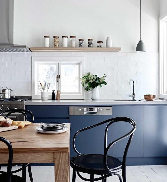 meuble bas cuisine bleu nuit avec une credence carrelage blanc étagère bois, ouverture salle à manger table bois et chaises noires en metal