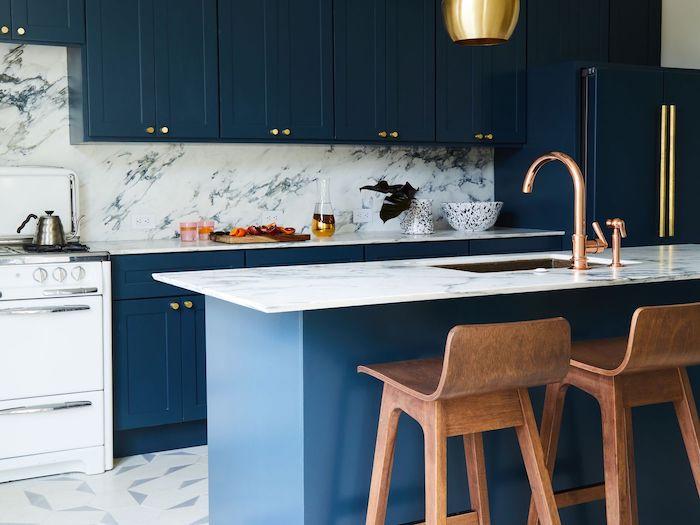 cuisine bleu marine et marbre avec des tabourets de bar bois, sol revetement gris et blanc, suspension or, robinetterie cuivre