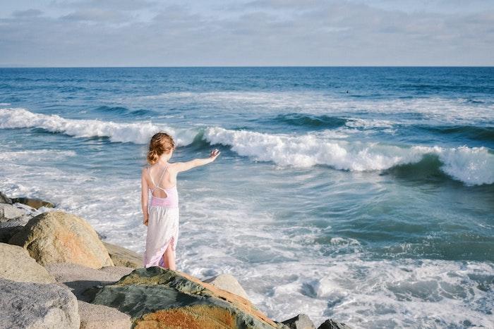 Au bord de la mer une fille robe rose et blanc, grandes ondes photo adorable, tresse indienne, coiffure pour fillette, comment faire une coiffure