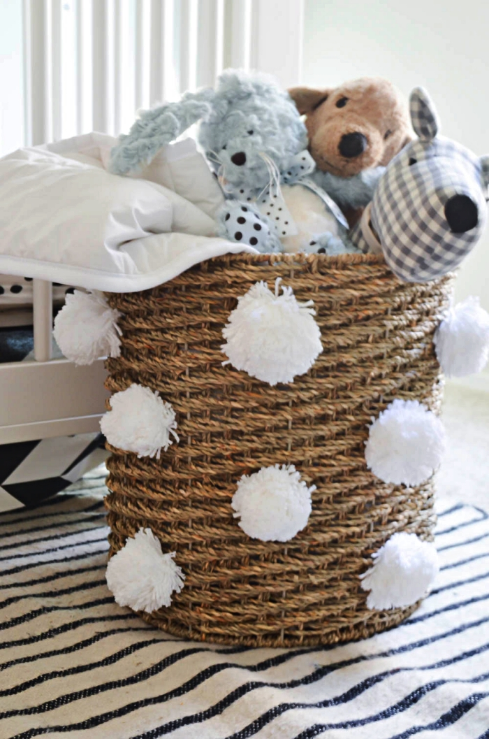 panier de rangement en osier décoré de pompons en laine blancs pour y stocker les peluches préférées de votre enfant