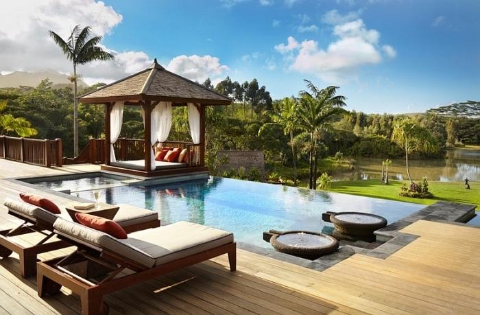 image piscine, comment décorer espace autour d'une piscine turquoise avec feu, modèle pergola exotique avec baldaquin