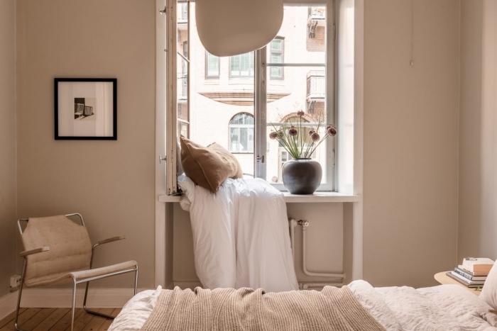 décoration petite chambre aux murs de peinture couleur sable avec fenêtre blanche, exemple de coin sous la fenêtre avec coussin marron et couverture blanche