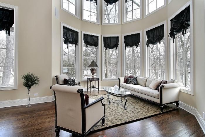 aménagement pièce au plafond haut, déco salon lumineux aux murs beige avec sol en planches bois foncé et meuble beige et noir