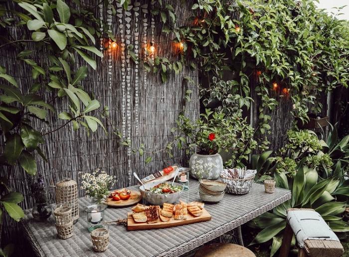 aménagement petit jardin avec clôture en bois et plantes grimantes, exemple éclairage de jardin avec guirlande lumineuse