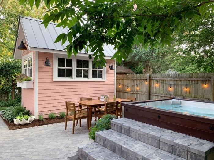 idée déco de jardin avec piscine, modèle de clôture en bois décorée avec guirlande lumineuse, meuble de jardin en bois
