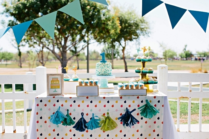 guirlande à fanions et tassels pour la deco anniversaire enfant, candy bar en plein air pour une pique-nique d'anniversaire 1 an