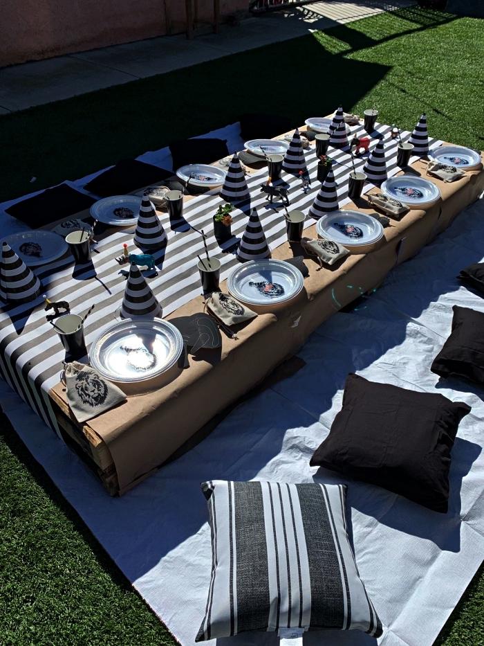 idée déco anniversaire pique-nique, déco de table de pique-nique en palette couverte de nappe beige et chemin de table à rayures