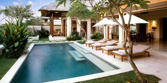 décoration jardin vert avec grande piscine et terrasse en carrelage blanc, modèle de transats piscine en bois et blanc