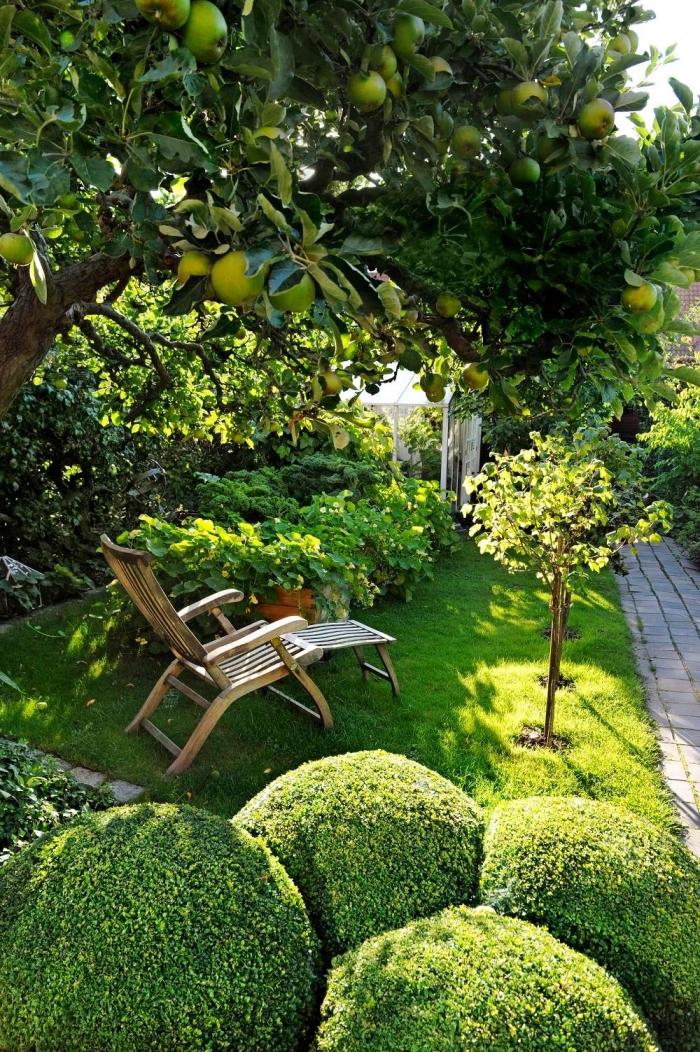 exemple comment aménager un petit jardin avec pelouse et arbres, mobilier de jardin à design pliant en bois foncé