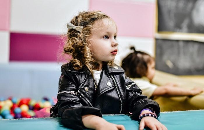 Idée mignonne de coiffure avec ruban sur les cheveux bouclés, fille veste cuir noir, coupe de cheveux petite fille, coiffure enfant, coiffure fillette