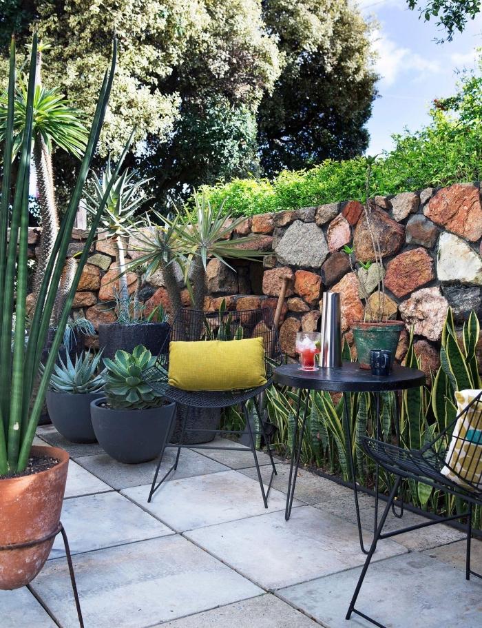 idée amenagement jardin paysager avec meubles de repos, plantes vertes exotiques pour un petit jardin à sol en dalles