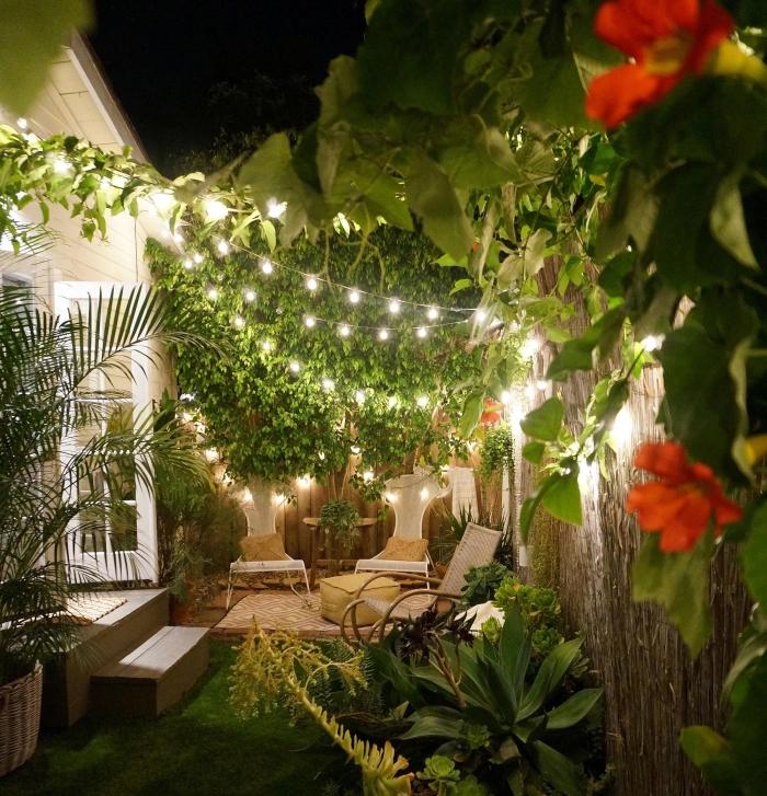 ambiance romantique dans un petit jardin avec clôture en bois, tapis beige et blanc sur sol bois extérieur décoré avec pouf