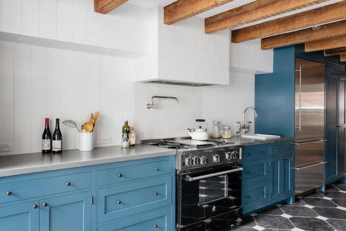 poutres apparentes dans une cuisine en bleu, carrelage mural blanc, plan de travail gris, electromenager noir et gris, cuisine vintage originale