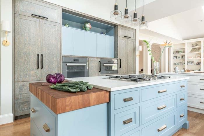 meuble haut et ilot central bleu clair, armoire de cuisine grise, parquet bois clair, suspensions industrieles