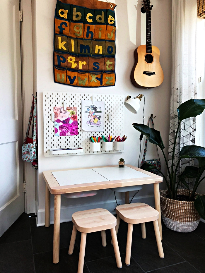 coin de jeu dans la chambre d'enfant avec petite table basse, tabourets en bois rangement dessins en tableau perforé