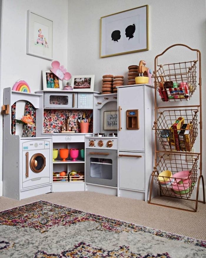 coin de jeu avec cuisine enfant et rangement jouet métallique avec trois paniers sur support