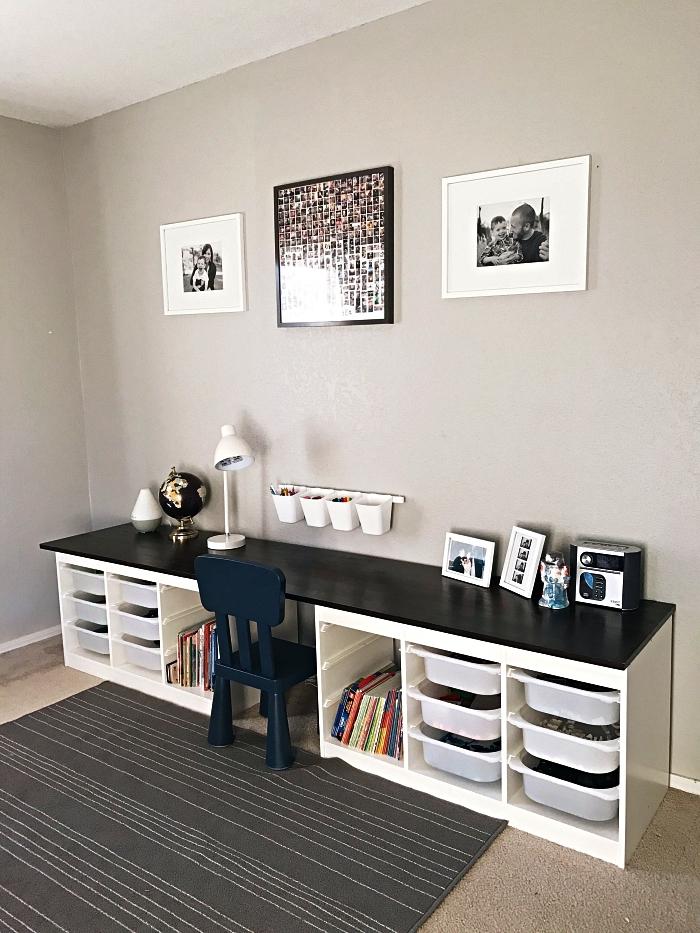 meuble de rangement avec bacs qui fait office de bureau et de table de jeux dans la chambre d'enfant