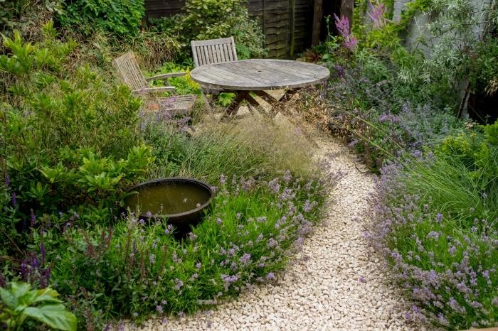 aménagement de petit jardin, décoration extérieure avec galets et plantes verts, meubles de jardin en bois foncé