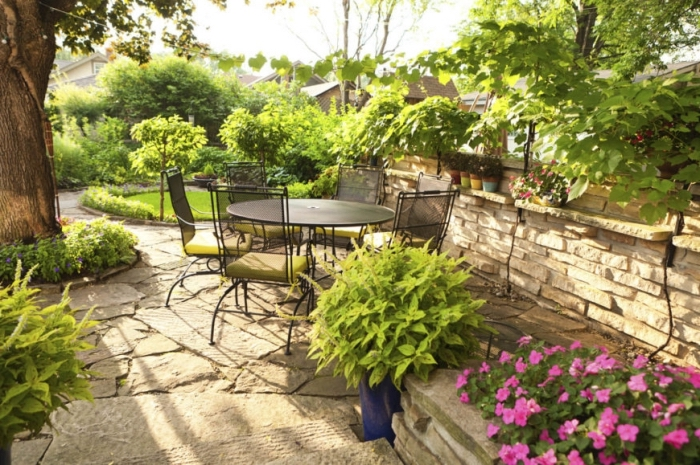 comment aménager son jardin, cour arrière avec coin de repos aménagé avec meubles en fer table ronde et chaises