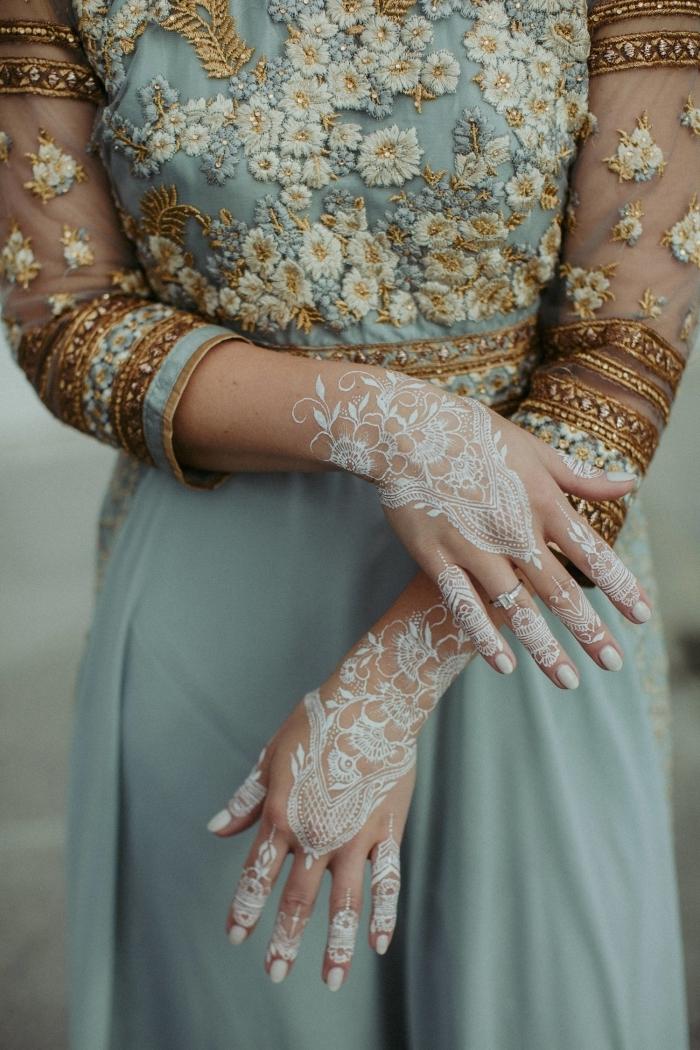 modele henné pour mariage, idée tatouage temporaire aux motifs floraux et feuilles, exemple dessin blanc sur main