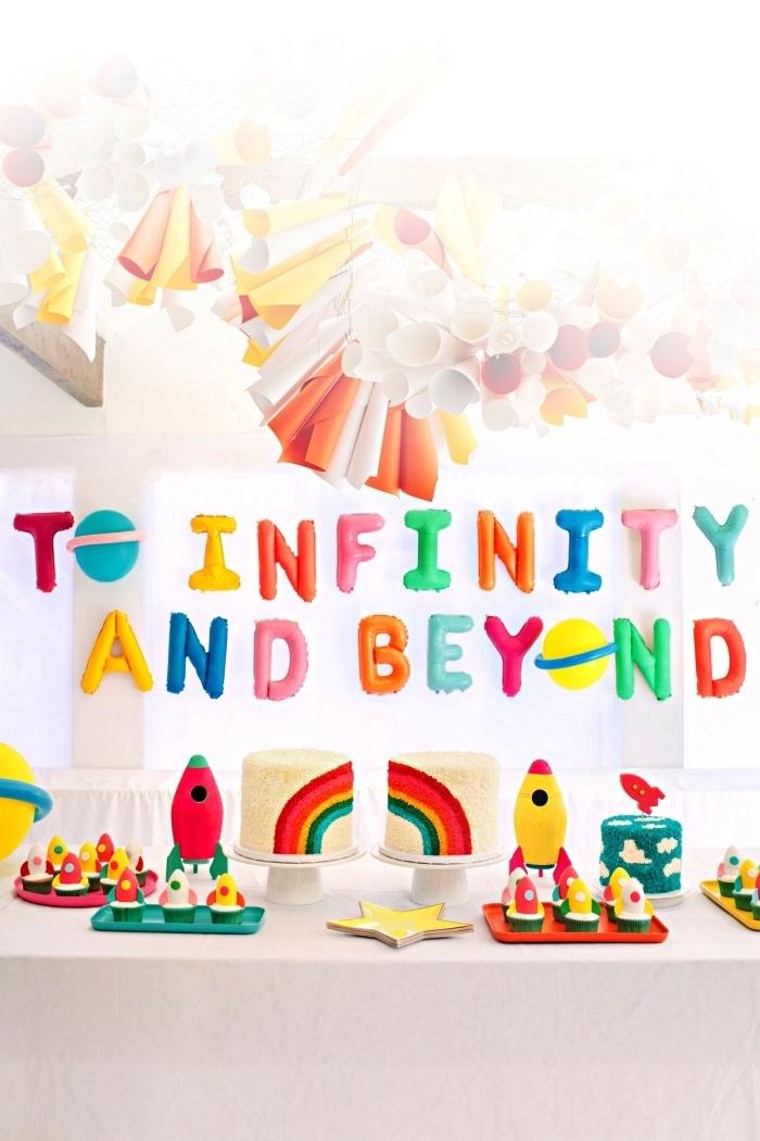 deco table anniversaire sur le thème espace avec ballons lettres colorés et une guirlande en papier, candy bar sur le thème de l'espace