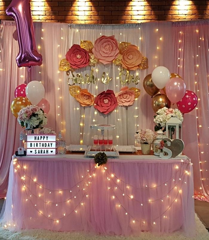 deco table anniversaire 1 an rose, table d'anniversaire fille décorée de guirlande led, jupe de table en tulle, ballons et fleurs